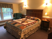An upstairs room with a queen bed, cozy colors, and quilts. This room offers a bath with a five-foot walk-in shower.